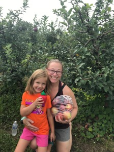 Becky (right) and daughter Delaney (left) with a bag of apples in an apple orchard